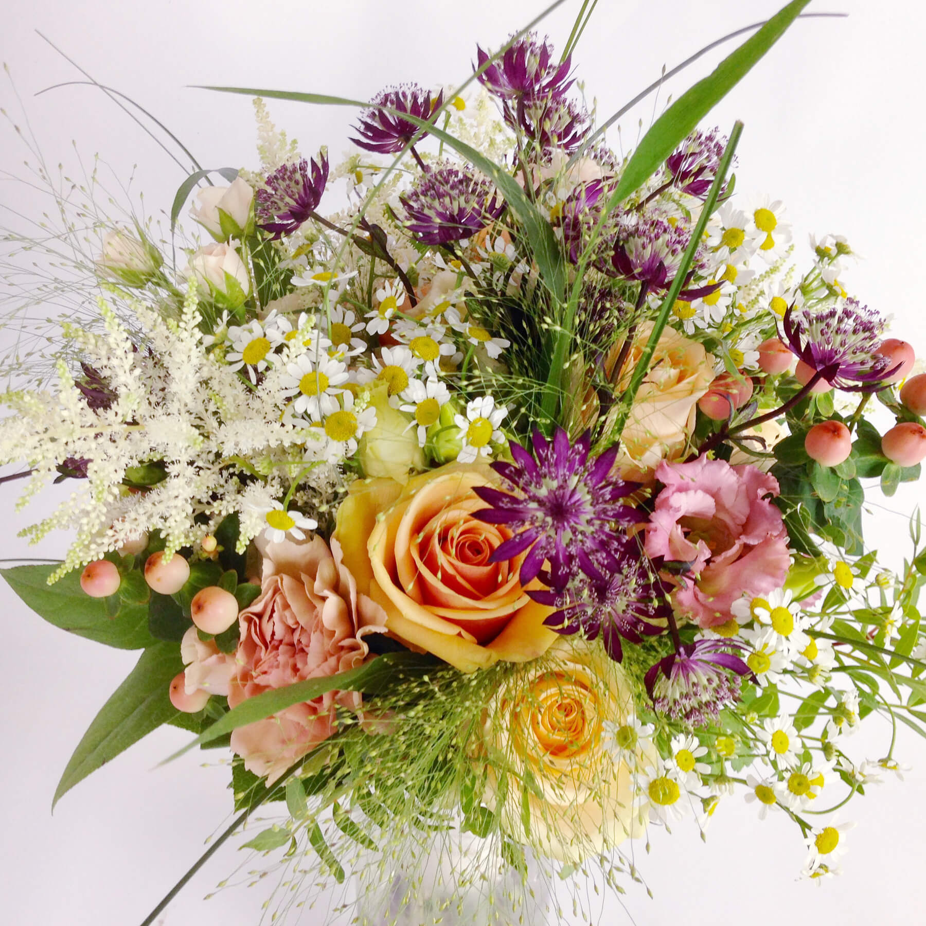 En somrig och härlig bukett med ljusa färger och ängslika blommor.