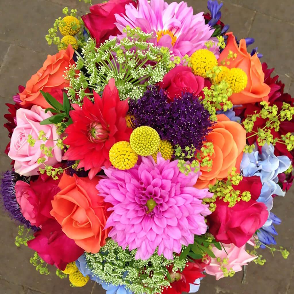 Flower power! Färgstark rundbunden brudbukett. Många färger och sorter i en kompakt och samlad klotform. Dahlior, rosor, ammi majus, trachelium och daggkåpa. De gula bollarna heter craspedia och är det lilla extra i denna bukett.