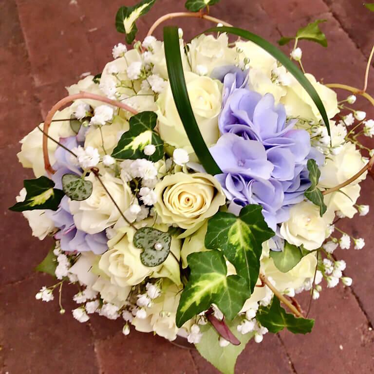 Blommor till bröllop: Kompakt brudbukett i vitt och ljuslila. Vita rosor dominerar. Ljuslila hortensia, vit brudslöja kompletterar. Vita pärlor, texasgräs, brokbladig murgröna samt hjärta på tråd gör buketten till ett vackert smycke som matchar bruden.