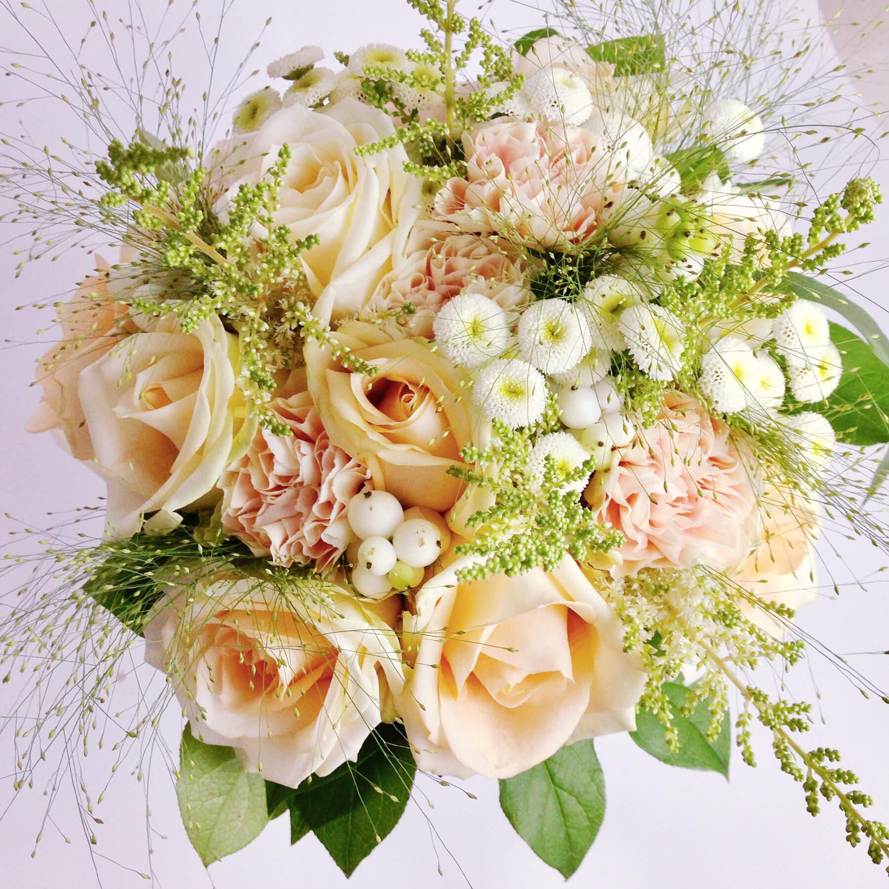 Rundbunden brudbukett i ljust aprikos och vitt. Floristen har använt sig av rosor, nejlikor, tanacetum, astilbe, fontängräs mm.