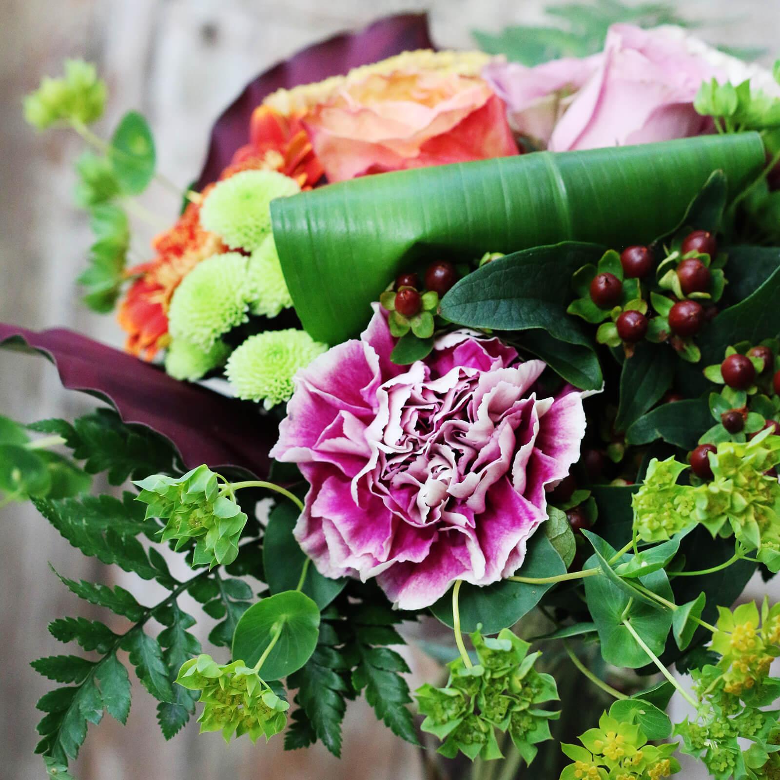 Kompakt bukett med blandade blommor.