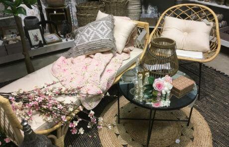 En del av interiöravdelningen: Här ser vi möbler, kuddar, korgar, korgstol, soffbord, lykta, mattor och sidenblommor.