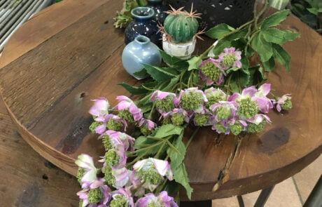 Ljuslila sidenblommor och minivaser på ett satsbord av trä.