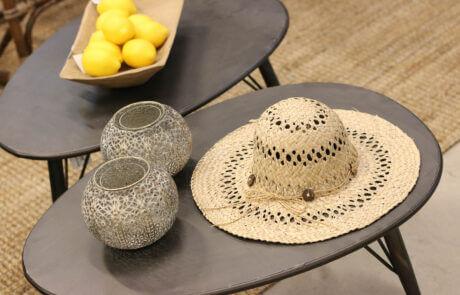 Detalj av interiör: små bord med ljuslyktor, en solhatt och gula citroner.
