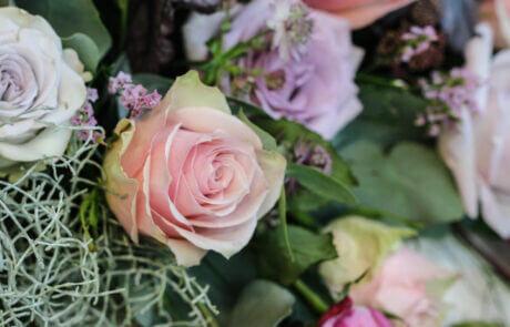 Ett arrangemang av snittblommor: Rosor i pastellfärger.