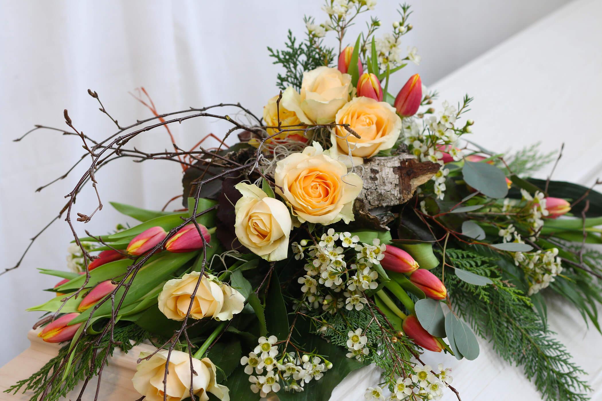 Denna kistdekoration bygger på mycket naturmaterial. Med näver, björkris och vaxblomma som bas har vi lagt till aprikos rosor och tulpaner. Det hela får en känsla av vår och natur. Blommorna varierar vi efter säsong.