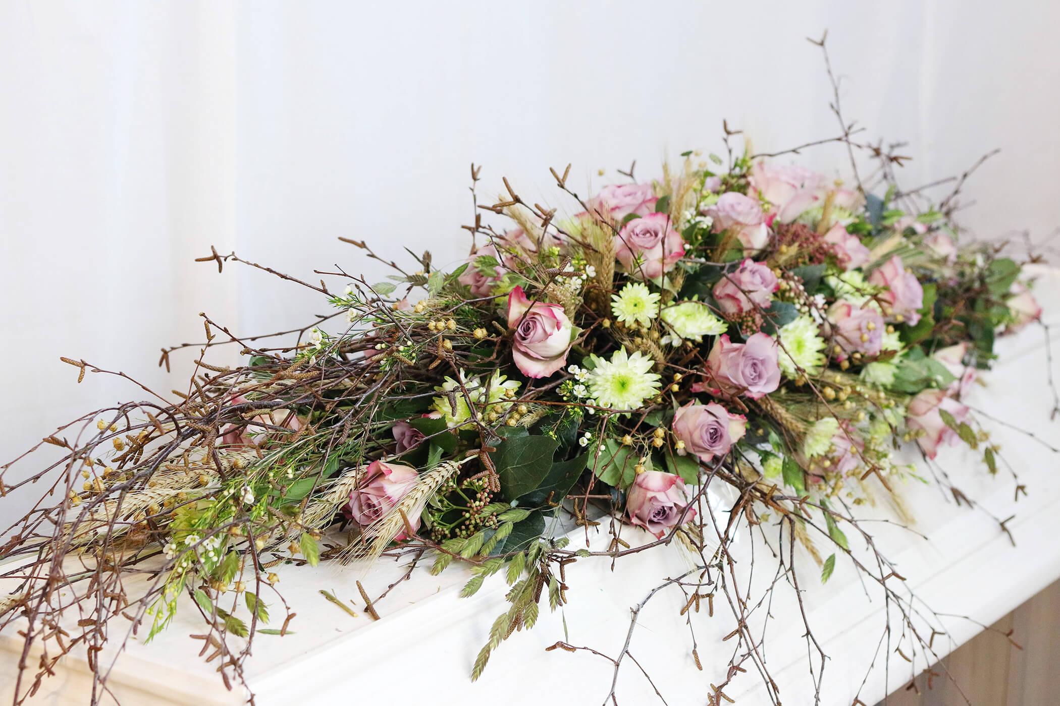 Denna naturnära kistdekoration är gjord av bleklila rosor, björkris och limefärgad krysantemum. Blommorna varierar efter säsong.