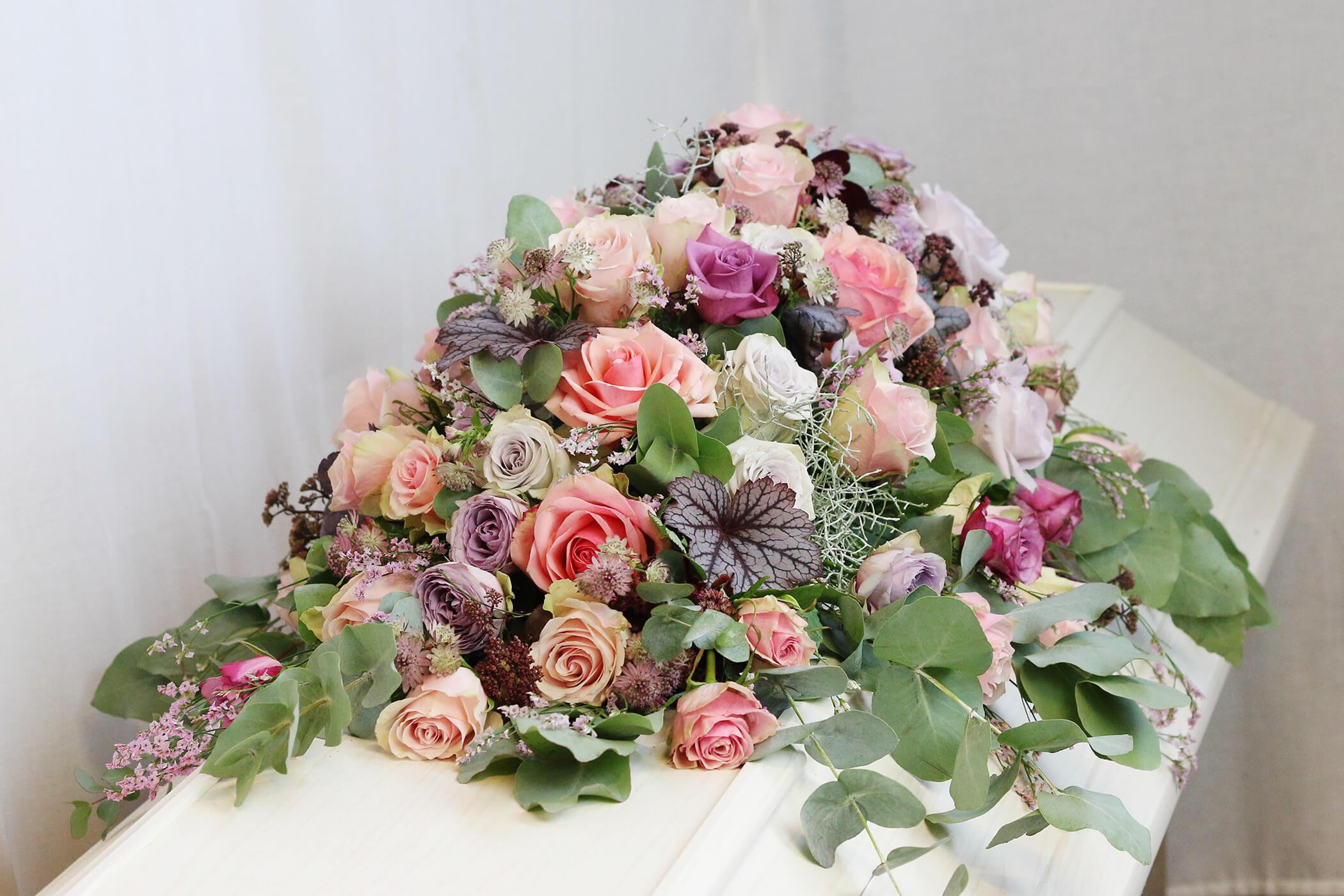 Denna kistdekoration har en mild färgskala i pasteller. Blekt rosa, lila och vitt ramas in av eucalyptus i grågrönt. Blommorna varierar efter säsong men just här har vi använt rosor, stjärnflocka, alunrot och silvergirland.