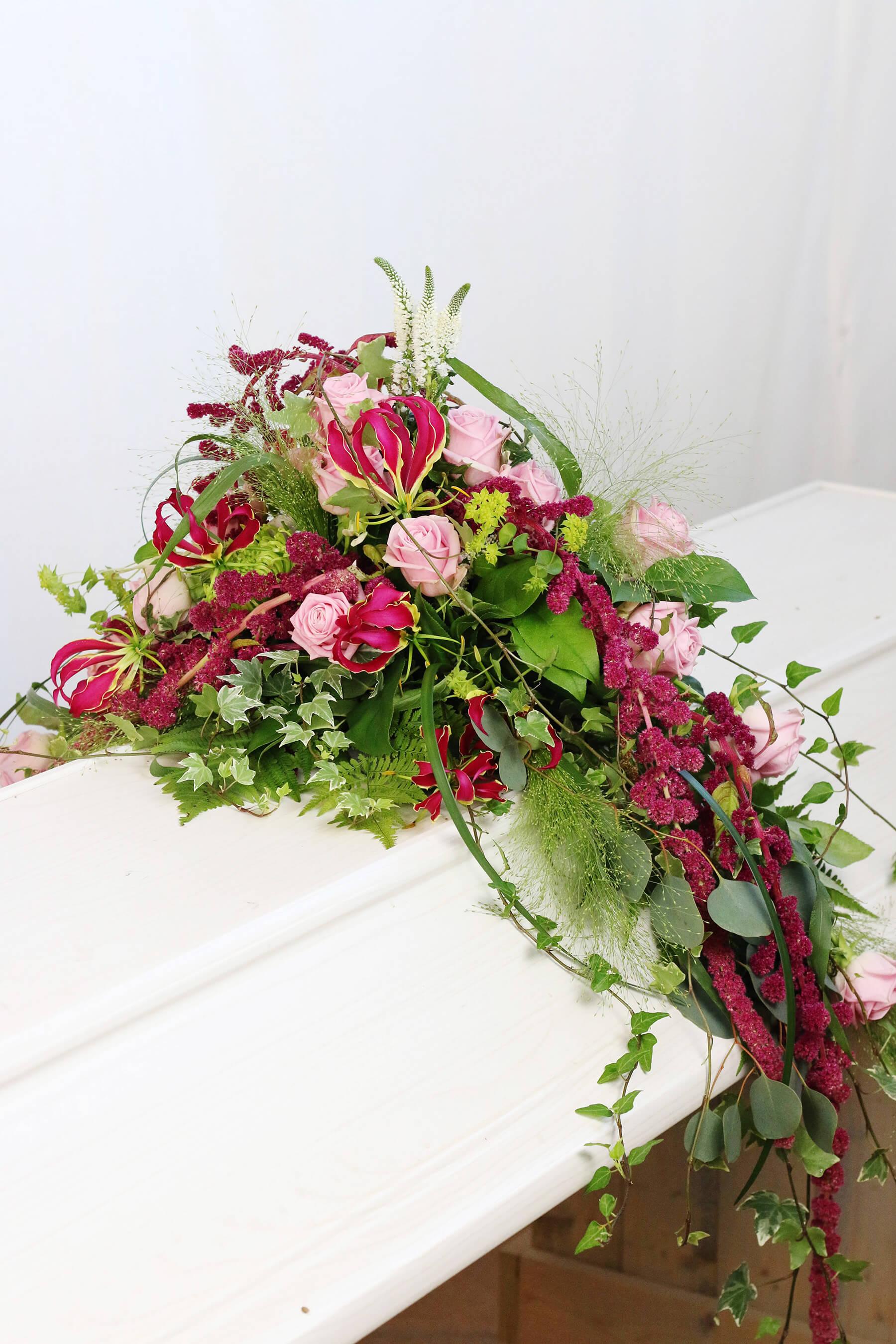 En personlig kistdekoration, där de röda blommorna hänger ner på sidorna. Blommorna varierar efter säsong. Här har vi använt oss av gloriosa, rävsvans, rosor och vackert grönt.