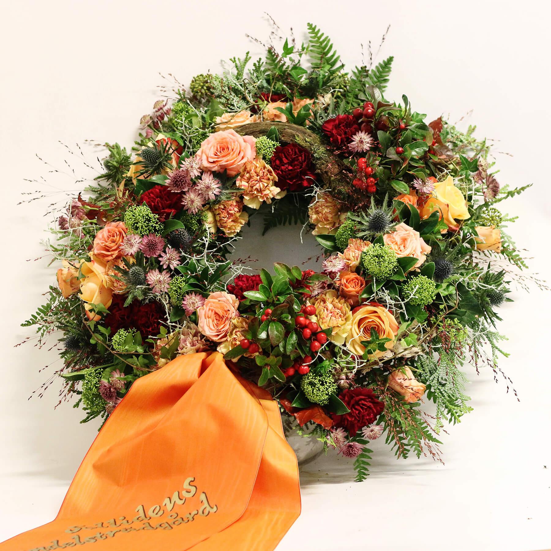 En magiskt vacker, rundbunden krans till begravning, skapad av våra florister. Med blandade blommor i milda färger blir det en fin enhet. Blommorna varierar men just här har vi använt rosor, nejlikor, skimmia, stjärnflocka, tistel mm.