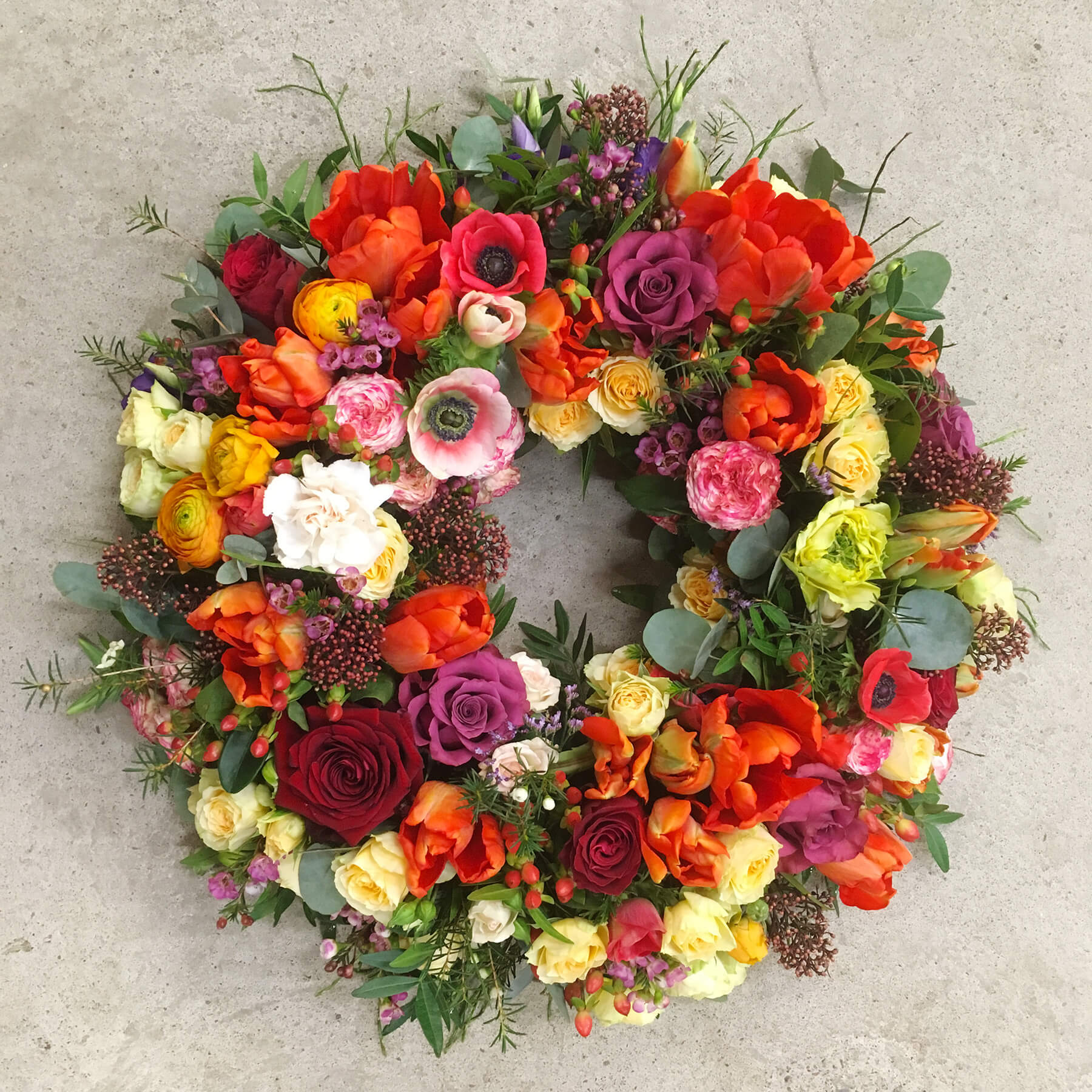 En magiskt vacker, rundbunden krans till begravning, skapad av våra florister. Med blandade blommor i varma färger blir det en fin enhet i rött, rosa, orange och gult. Blommorna varierar men just här har vi använt rosor, nejlikor, skimmia, tulpaner och vaxblomma mm.