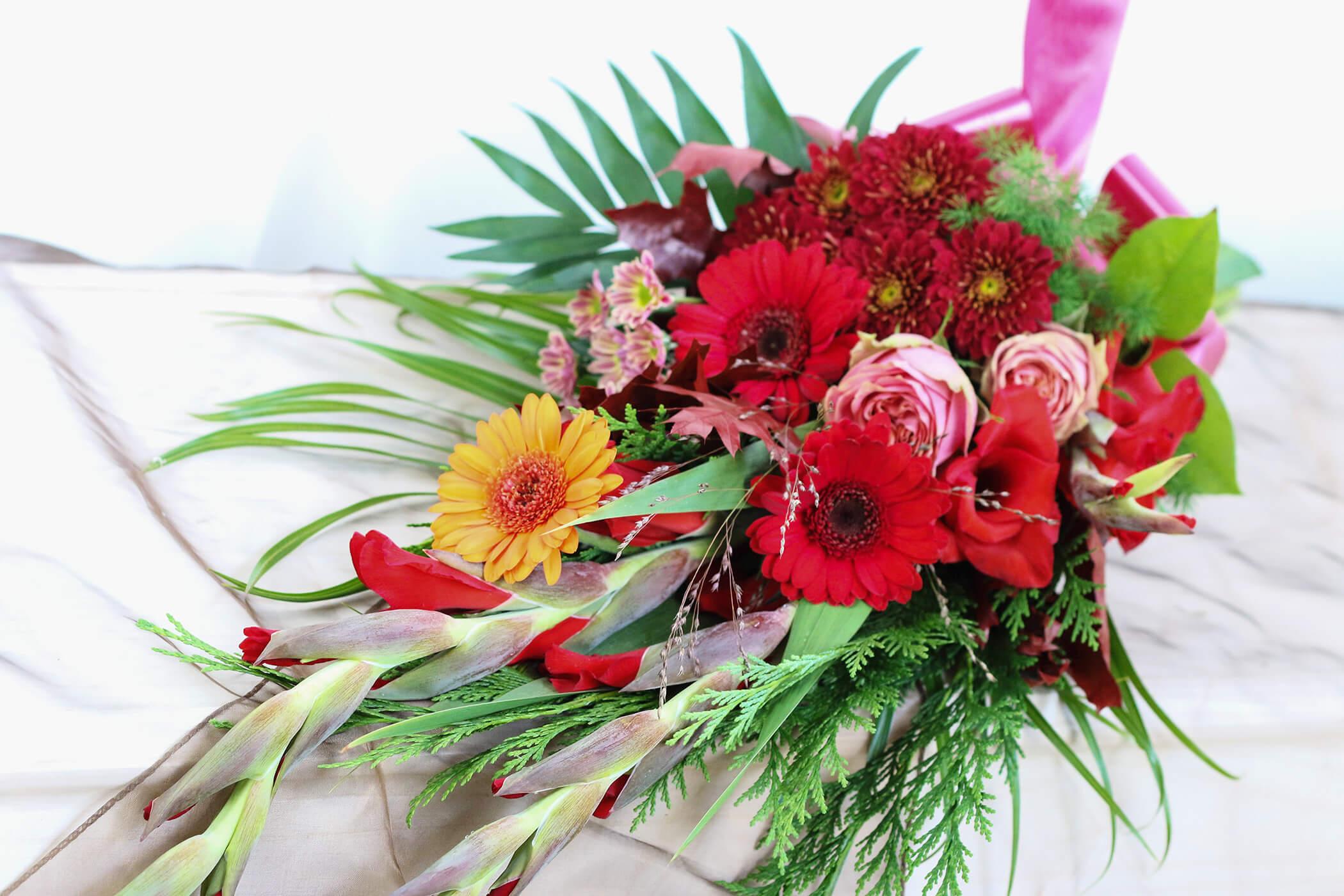 Blommor i varma röda och rosa färger dominerar denna sorgbukett. Blommorna varierar vi efter säsong. Här har vi använt rosor, krysantemum, germini och vackert grönt.