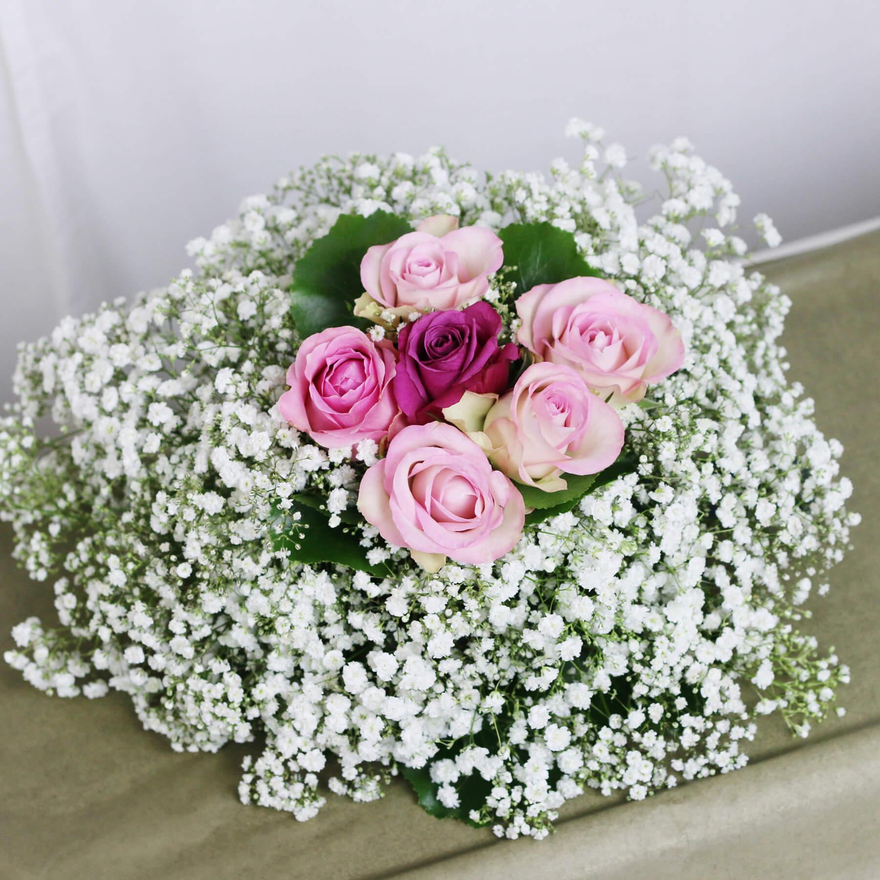 En liten, skir sorgdekoration med rosa rosor omslutna av vit brudslöja. Vackert i all sin enkelhet.